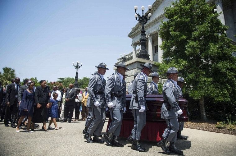 As lawmakers, family and friends follow, the South Carolina Highway Patrol Honor Guard carry the coffin of church pastor and South Carolina State Sen. Clementa Pinckney to lie in repose at the Statehouse Rotunda on June 24, 2015 in Columbia, South Carolina. Pinckney was one of nine people killed during a Bible study inside Emanuel AME church in Charleston. Pressure is growing in South Carolina to take down the Confederate flag that has flies on the front lawn of its State House in Columbia, also alongside a Confederate war memorial. (Jim Watson/AFP/Getty Images)