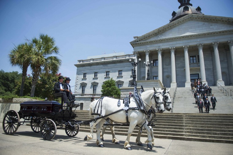 Members of the South Carolina State Legislature walk out as the casket of church pastor and South Carolina State Sen. Clementa Pinckney arrives at the Statehouse on June 24, 2015 in Columbia, South Carolina. Pinckney was one of nine people killed during a Bible study inside Emanuel AME church in Charleston. Pressure is growing in South Carolina to take down the Confederate flag that has flies on the front lawn of its State House in Columbia, also alongside a Confederate war memorial. (Jim Watson/AFP/Getty Images)