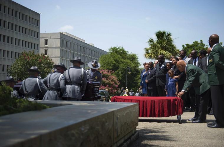 As lawmakers, family and friends watch, the South Carolina Highway Patrol Honor Guard arrive with the coffin of church pastor and South Carolina State Sen. Clementa Pinckney at the Statehouse on June 24, 2015 in Columbia, South Carolina. Pinckney was one of nine people killed during a Bible study inside Emanuel AME church in Charleston. Pressure is growing in South Carolina to take down the Confederate flag that has flies on the front lawn of its State House in Columbia, also alongside a Confederate war memorial. (Jim Watson/AFP/Getty Images)