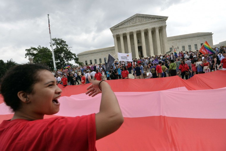 People wave a giant equality flag outside the Supreme Court in Washington, DC on June 26, 2015 after its historic decision on gay marriage. The US Supreme Court ruled Friday that gay marriage is a nationwide right, a landmark decision in one of the most keenly awaited announcements in decades and sparking scenes of jubilation. The nation's highest court, in a narrow 5-4 decision, said the US Constitution requires all states to carry out and recognize marriage between people of the same sex. (AFP Photo/P / )