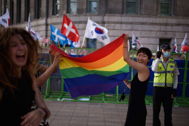 "Participants of a gay pride march wave a rainbow flag as they stand before a police cordon set up to keep out anti-gay Christian activists, in Seoul on June 28, 2015. Thousands of participants of South Korea's annual gay pride parade marched across central Seoul, with many celebrating the US Supreme Court's historic decision allowing same-sex couples to wed. Gay and transgender Koreans live largely under the radar in a country that remains deeply conservative about matters of sexual identity and where many still regard homosexuality as a foreign phenomenon. Thousands of Christian activists stood behind police barriers to wave banners and chant slogans at those taking part, condemning what they called an attempt to turn the South Korean capital into ""Sodom and Gomorrah."" (Ed Jones/AFP/Getty Images)"
