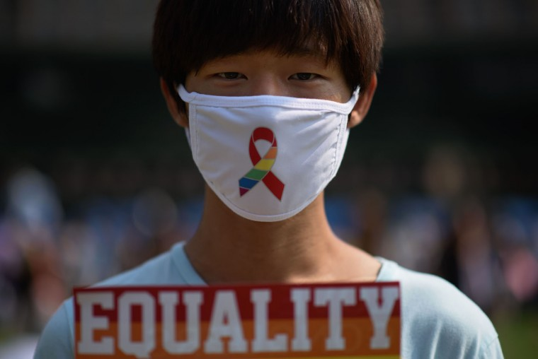 "An attendee poses for a photo prior to a gay pride march held as part of the 'Korea Queer Festival' in Seoul on June 28, 2015. Thousands of participants of South Korea's annual gay pride parade marched across central Seoul, with many celebrating the US Supreme Court's historic decision allowing same-sex couples to wed. Gay and transgender Koreans live largely under the radar in a country that remains deeply conservative about matters of sexual identity and where many still regard homosexuality as a foreign phenomenon. Thousands of Christian activists stood behind police barriers to wave banners and chant slogans at those taking part, condemning what they called an attempt to turn the South Korean capital into ""Sodom and Gomorrah."" (Ed Jones/AFP/Getty Images)"