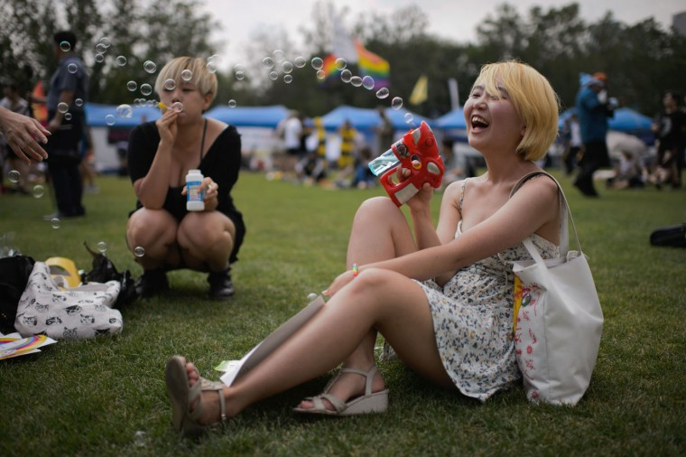 "Attendees laugh as they blow bubbles during a gay pride event held as part of the 'Korea Queer Festival' in Seoul on June 28, 2015. Thousands of participants of South Korea's annual gay pride parade marched across central Seoul, with many celebrating the US Supreme Court's historic decision allowing same-sex couples to wed. Gay and transgender Koreans live largely under the radar in a country that remains deeply conservative about matters of sexual identity and where many still regard homosexuality as a foreign phenomenon. Thousands of Christian activists stood behind police barriers to wave banners and chant slogans at those taking part, condemning what they called an attempt to turn the South Korean capital into ""Sodom and Gomorrah."" (Ed Jones/AFP/Getty Images)"