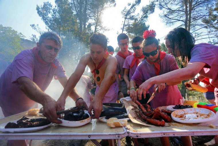 "Covered in wine, revelers prepare ""chorizo"" (spicy pork sausage) and ""morcilla"" (blood sausage) during the""Batalla del Vino"" (Battle of Wine) in Haro, on June 29, 2015. (CESAR MANSO/AFP/Getty Images)"