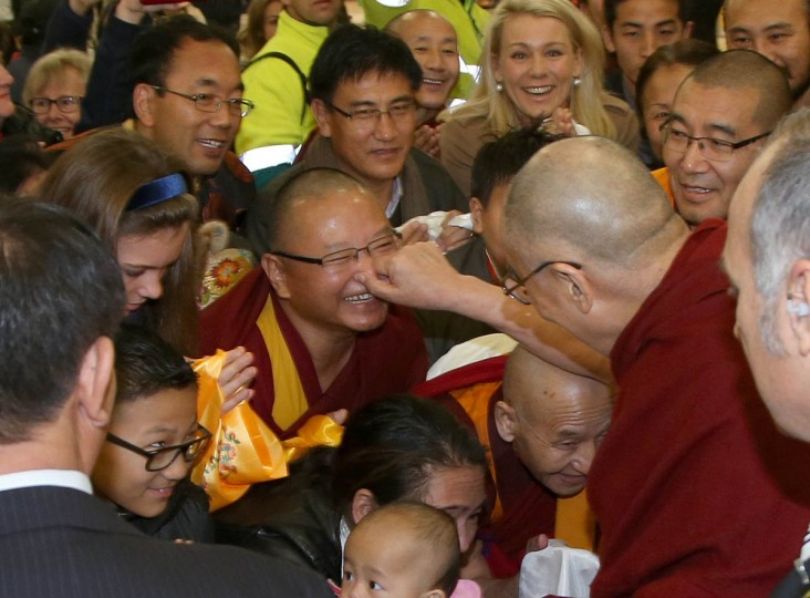 The Dalai Lama, center right, pinches the nose of a well-wisher as he arrives in Sydney. The Tibetan spiritual leader is visiting Australia for the 10th time. (Rick Rycroft/AP photo)
