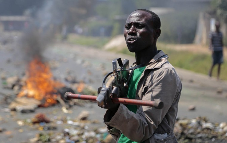 An opposition demonstrator points a mock gun made from wood towards soldiers and tells them it is shameful to shoot on people who cannot defend themselves, in the Ngagara neighborhood of the capital Bujumbura, in Burundi. Demonstrators opposed to President Pierre Nkurunziza running for a third term tried to march but were prevented by police and soldiers firing tear gas, so erected a burning barricade in their neighborhood instead. (Gildas Ngingo/AP photo)
