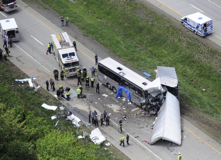 Authorities investigate the scene of a fatal collision between a tractor-trailer and a tour bus on Interstate 380 near Mount Pocono, Pa. Multiple people were killed more than a dozen were sent to hospitals. (David Kidwell/AP photo)
