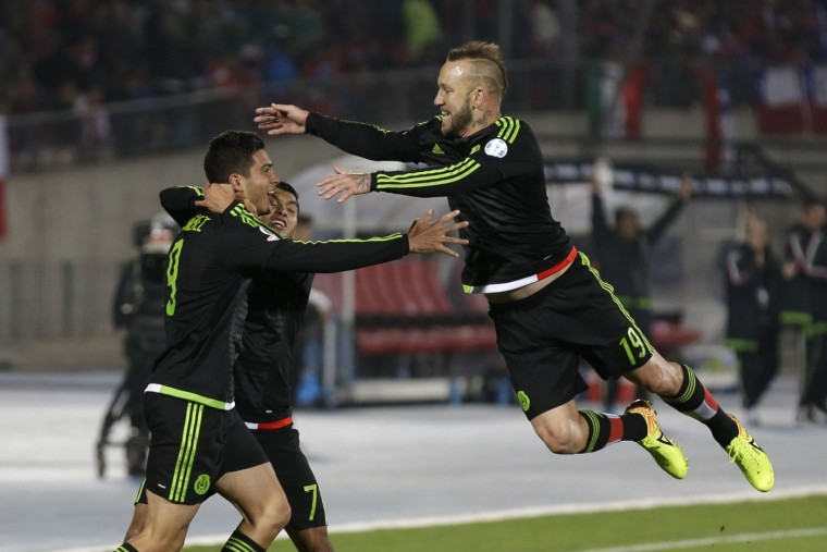 Mexico's Raul Jimenez, left, celebrates after scoring his side's second goal against Chile, with teammates Jesus Corona, center, and Matias Vuoso during a Copa America Group A soccer match at El Nacional stadium in Santiago, Chile, Monday, June 15, 2015. (AP Photo/Natacha Pisarenko)