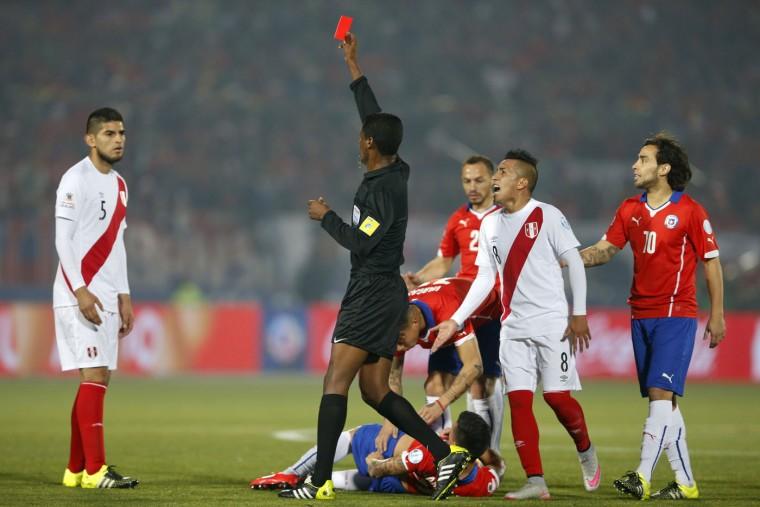 Referee Jose Argote, center, shows the red card to Peru's Carlos Zambrano, left, as Chile's Charles Aranguiz, bottom, lies on the ground during a Copa America semifinal soccer match at the National Stadium in Santiago, Chile, Monday, June 29, 2015. (AP Photo/Andre Penner)