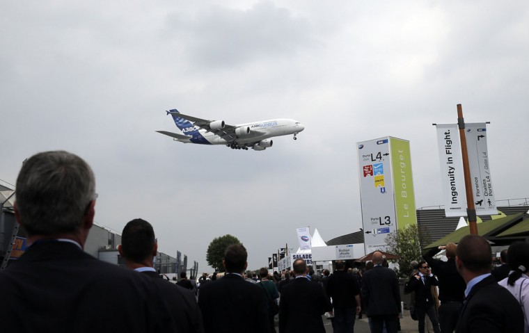 Visitors watch an Airbus A380 during a demonstration flight of the Paris Air Show, at Le Bourget airport, north of Paris, Monday, June 15, 2015. Some 300,000 aviation professionals and spectators are expected at this weekís Paris Air Show, coming from around the world to make business deals and see dramatic displays of aeronautic prowess and the latest air and space technology. (AP Photo/Christophe Ena)