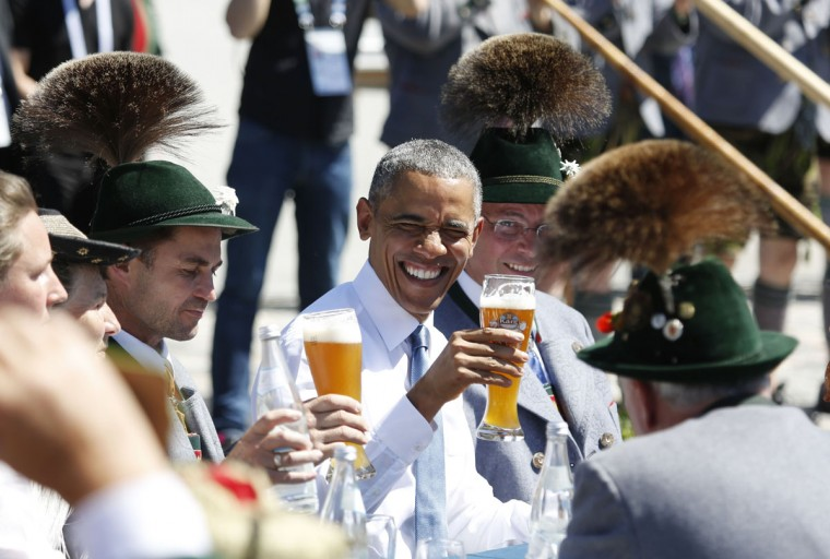 U.S. President Barack Obama, center, toasts with a beer as he sits between men dressed in traditional Bavarian clothes during a visit to the village of Kruen, southern Germany, Sunday, June 7, 2015 prior to the G-7 summit in Schloss Elmau hotel near Garmisch-Partenkirchen where the summit will start later the day. (AP Photo/Markus Schreiber)