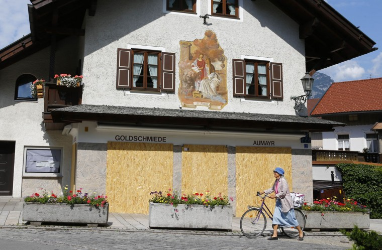 A woman pushes her bike past a jeweler's shop that is protected with wooden boards prior to a protest in Garmisch-Partenkirchen, southern Germany, Saturday, June 6, 2015 against the G-7 summit in nearby Schloss Elmau hotel on June 7/8. (AP Photo/Matthias Schrader)