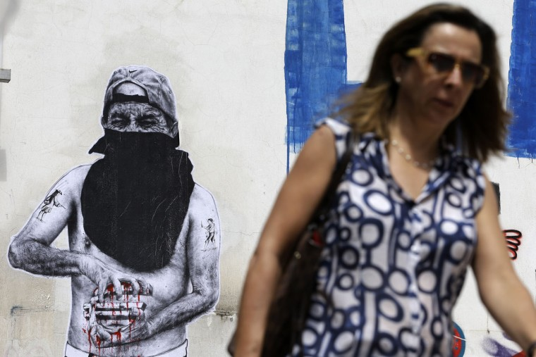 A pedestrian passes graffiti, depicting a protester squeezing a Euro, in Athens Monday, June 22, 2015. European officials were cautious about the prospects of reaching a comprehensive deal on Monday to keep Greece from defaulting and falling out of the currency union, despite optimism in financial markets. (AP Photo/Thanassis Stavrakis)