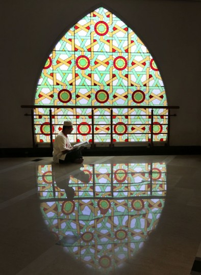 A Muslim man reads the holy book of Quran at a mosque during the second week of Ramadan in Jakarta, Indonesia, Monday, June 29, 2015. Muslims across the world are observing the holy fasting month of Ramadan, where they refrain from eating, drinking and smoking from dawn to dusk. (AP Photo/Tatan Syuflana)