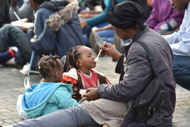 A migrant woman feeds a child after they were disembarked from the British Royal Navy ship HMS Bulwark at Catania harbor, Italy, Monday, June 8, 2015. Over the last weekend, nearly 6,000 migrants were rescued by an array of European military vessels, including 2,371 who were saved on Sunday from 15 boats that ran into difficulty shortly after smugglers set off with them from Libyan shores, the Italian coast guard said. (AP Photo/Carmelo Imbesi)
