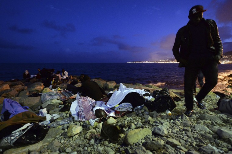 Migrants sleep on the rocks by the sea in Ventimiglia, at the border between Italy and France, early Monday, June 15, 2015. A standoff between nearly 200 migrants and the French border police has entered its fourth day with would-be refugees refusing to leave Italy's Mediterranean border with France in hopes of continuing their journeys north. (AP Photo/Massimo Pinca)