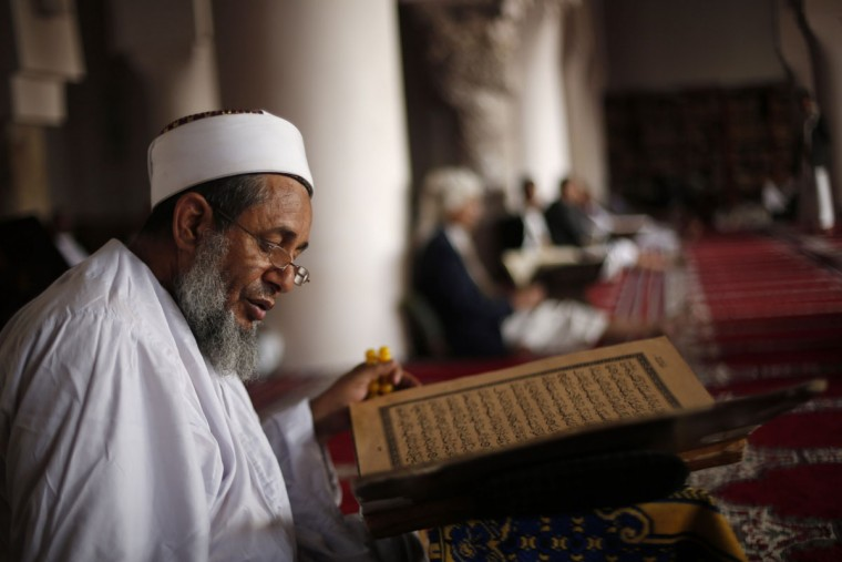 An elderly man reads verses of the Quran, Islam's holy book, on the first day of the fasting month of Ramadan in the Grand Mosque in the old city of Sanaa, Yemen, Thursday, June 18, 2015. The fast is intended to bring the faithful closer to God and to remind them of the suffering of those less fortunate. Muslims often donate to charities during the month and feed the hungry. (AP Photo/Hani Mohammed)