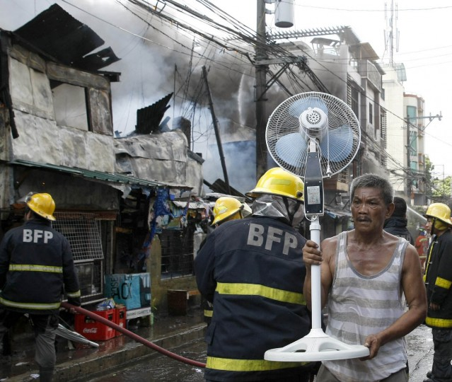 A resident saves an electric fan as firemen battle a fire that engulfs a neighborhood of informal settlers in suburban Quezon city, northeast of Manila, Philippines. Fire officials say the fire gutted close to a hundred houses and affected around 300 families. The fire occurred three weeks after a footwear factory fire killed 72 people in suburban Valenzuela city, north of Manila, and prompted the Government to inspect 300,000 factories for compliance of fire safety rules. (Bullit Marquez/AP photo)