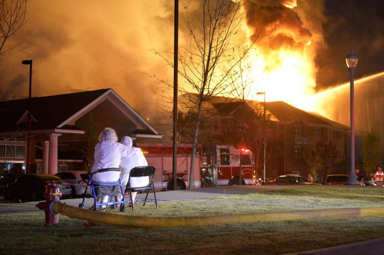 Residents watch as the Marshall Square Retirement Resort goes up in flames in Evans, Ga. Officials say two residents of Marshall Square retirement community are unaccounted for after fire destroyed much of the building in the morning, according to the Augusta Chronicle. More than 80 residents of the upscale retirement resort in the heart of Evans were forced to flee for safety when fire alarms went off between 3 and 3:30 a.m. (Michael Holahan /The Augusta Chronicle via AP)