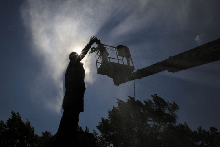 A worker washes a monument to famous Russian poet Aleksander Pushkin during preparations to celebrate the 216th anniversary of his birth in St. Petersburg, Russia. (Dmitry Lovetsky/AP photo)