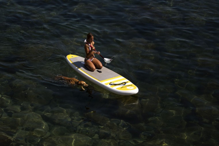 A woman paddles on top of a surfboard as her dog swims next to her in the Mediterranean Sea in Barcelona, Spain, Monday, June 29, 2015. Weather stations across Spain are warning people to take extra precautions as a heat wave engulfs much of the country, increasing the risk of wildfires. The country's meteorological agency says a mass of hot air originating in Africa is moving northwards, bringing with it until at least Monday temperatures reaching 40 C. (AP Photo/Emilio Morenatti)