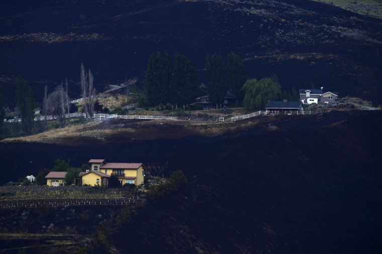 The close proximity that a wildfire encroached upon homes near Monitor, Wash., can be seen on Monday, June 29, 2015. The wildfires hit parts of central and eastern Washington over the weekend as the state is struggling with a severe drought. (Tyler Tjomsland/The Spokesman-Review, via AP)