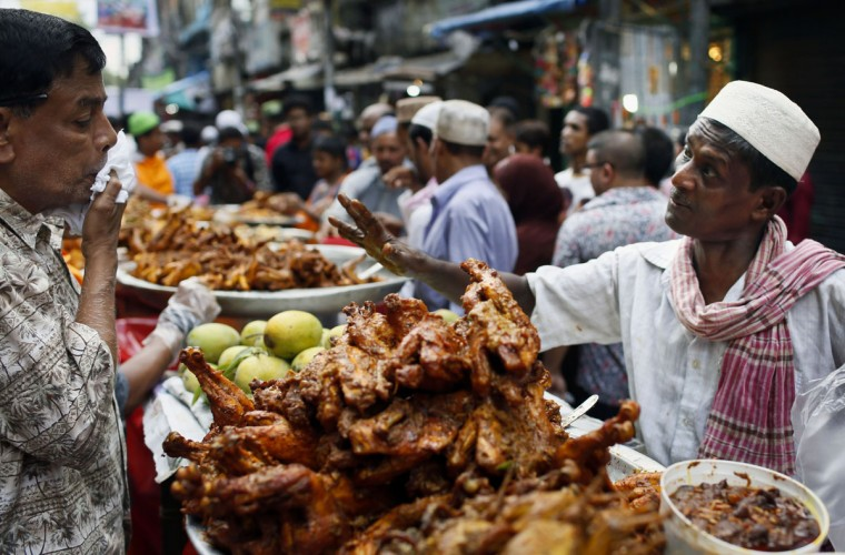A Bangladeshi vendor, right, sells food items for Iftar, the evening meal for breaking the daily fast at a market area on the first day of Ramadan in Dhaka, Bangladesh, Friday, June 19, 2015. Muslims across the world are observing the holy fasting month of Ramadan, where they refrain from eating, drinking and smoking from dawn to dusk. (AP photo/A.M. Ahad)