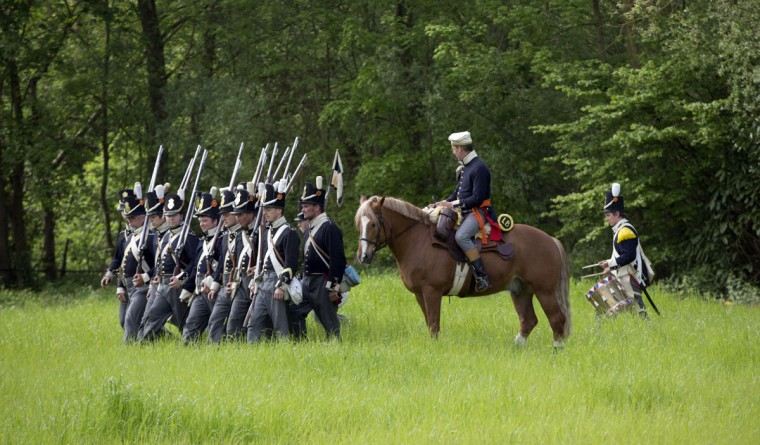 In this May 10, 2015, photo, historical re-enactors dressed as soldiers of the Belgian-Dutch 7th Battalion of the Line are commanded by a cavalry officer as they march in formation at a Napoleonic era living history camp in Elewijt, Belgium. The Belgian-Dutch living history group is coordinating their group for participation in the 200th anniversary of the Battle of Waterloo which will take place in June 2015. (AP Photo/Virginia Mayo)