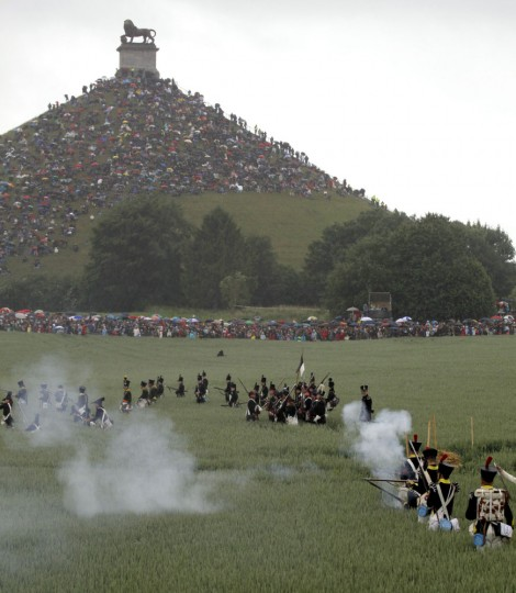 In this June 20, 2010 file photo, re-enactors participate in a mock battle in front of the Lion's Mound during a living history event of the 1815 Battle of Waterloo in Waterloo, Belgium. More than 5,000 Napoleonic era re-enactors will participate in the upcoming 200th anniversary of the Battle of Waterloo which takes place in June 2015. (AP Photo/Virginia Mayo, File)