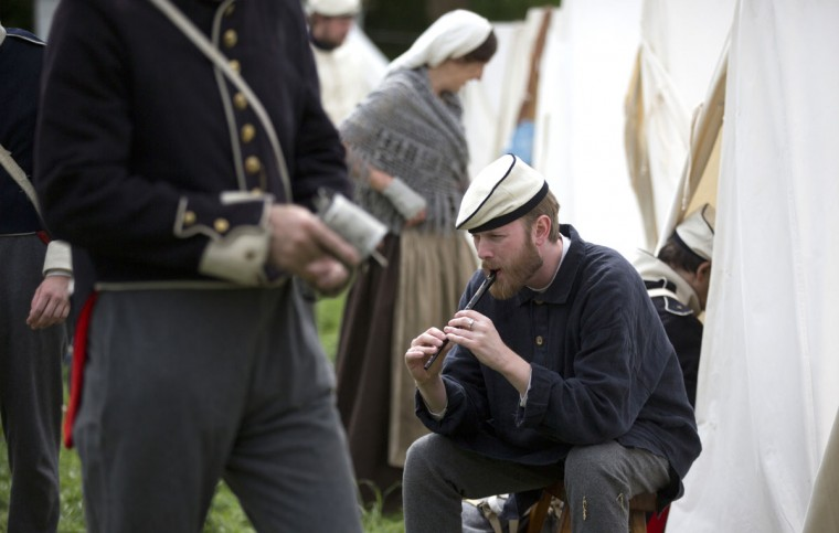In this May 9, 2015, photo, an historical re-enactor dressed as a soldier of the Belgian-Dutch 7th Battalion of the Line plays the flute at a Napoleonic era living history camp in Elewijt, Belgium. The Belgian-Dutch living history group is coordinating their group for participation in the 200th anniversary of the Battle of Waterloo which will take place in June 2015. (AP Photo/Virginia Mayo)