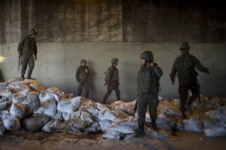 "Brazilian Army soldiers walk on a pile of sandbags during the dismantling of one of their bases in the Mare slum complex in Rio de Janeiro, Brazil, Tuesday, June 30, 2015. The last soldiers and marines occupying the Mare complex of slums will be replaced by police as part of the program to ""pacify"" and reduce violence in the favela. The process started in April with a June 30 deadline for the army to vacate the neighborhood. (AP Photo/Felipe Dana)"