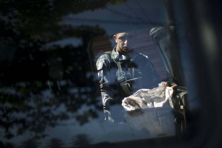"Seen through a car window, a police officer carries a bag of drugs seized during a police operation at the Mare slum complex in Rio de Janeiro, Brazil, Tuesday, June 30, 2015. The last soldiers and marines occupying the Mare complex of slums will be replaced by police as part of the program to ""pacify"" and reduce violence in the favela. The process started in April with a June 30 deadline for the army to vacate the neighborhood. (AP Photo/Felipe Dana)"