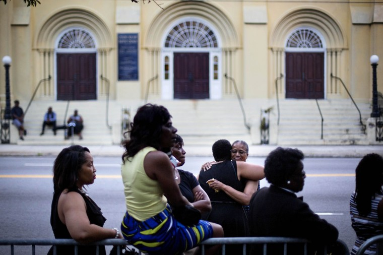 Lauretta Geddis, of Charelston, S.C., rear right, embraces Brenda T. Williams, of North Charelston, while waiting on line to enter Sen. Clementa Pinckney's funeral service, Friday, June 26, 2015, in Charleston. President Barack Obama will deliver the eulogy at Pinckney's funeral Friday at a nearby college arena. (AP Photo/David Goldman)