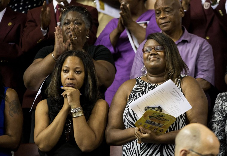 Mourners stand up to applaud Sen. Clementa Pinckney during his funeral service, Friday, June 26, 2015, in Charleston, S.C. President Barack Obama will deliver the eulogy at Pinckney's funeral Friday at College of Charleston's TD Arena near the Emanuel AME Church, the scene of last week's shooting. (AP Photo/David Goldman)