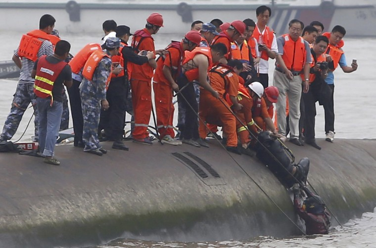 Rescuers help lift a survivor pulled from the capsized cruise ship on the Yangtze River in Jianli in central China's Hubei province Tuesday June 2, 2015. Divers on Tuesday pulled survivors from inside the overturned cruise ship, state media said, giving some small hope to an apparently massive tragedy with well over 400 people still missing on the river. (Chinatopix Via AP)