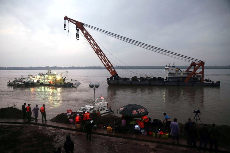 A crane is positioned near a capsized ship on the Yangtze River in Jianli in central China's Hubei province Tuesday June 2, 2015. Divers on Tuesday pulled three people alive from inside an overturned cruise ship and searched for other survivors, state media said, giving some small hope to an apparently massive tragedy with well over 400 people still missing on the Yangtze River. (Chinatopix Via AP)