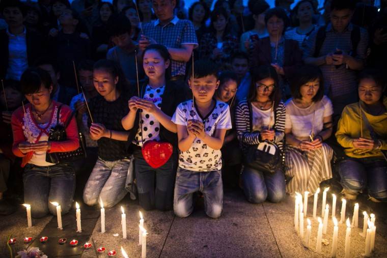 Locals and relatives of passengers onboard the capsized cruise ship pray during a candle light vigil in Jianli county, in southern China's Hubei province, Thursday June 4, 2015. Rescuers cut three holes into the overturned hull of a river cruise ship in unsuccessful attempts to find more survivors Thursday. (Chinatopix Via AP)