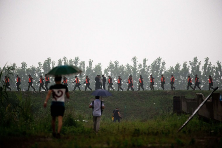 Chinese soldiers march along the embankment past police officers, at center, stopping journalists from getting near to a command center which has been set up for rescue operations of a capsized cruise ship on the Yangtze River in Jianli in central China's Hubei province, Tuesday, June 2, 2015. Divers on Tuesday pulled several survivors from inside the capsized cruise ship and searched for other survivors, state media said, giving some small hope to an apparently massive tragedy. (AP Photo/Andy Wong)