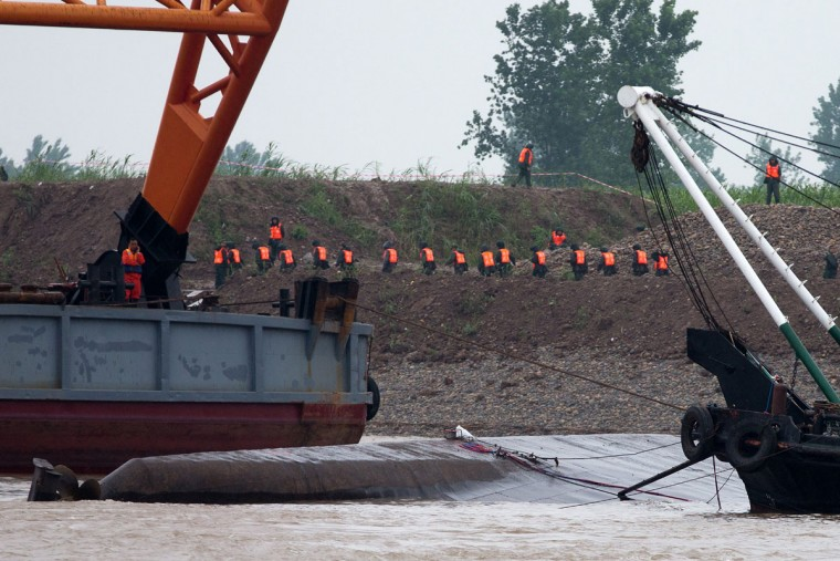 Chinese paramilitary policemen work on the river bank behind the capsized ship, center, on the Yangtze River in China's Hubei province, Wednesday, June 3, 2015. The capsizing late Monday of the multi-decked Eastern Star in the Yangtze River in southern China is on track to become the country's deadliest maritime disaster in seven decades. (AP Photo/Andy Wong)