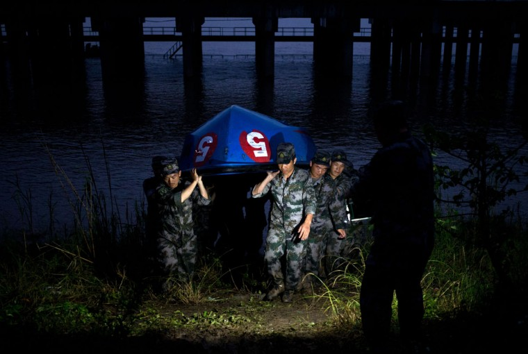 Chinese soldiers carry their boat to the embankment after their search and rescue operation near a capsized cruise ship on the Yangtze River in Jianli in central China's Hubei province, Tuesday, June 2, 2015. Divers on Tuesday pulled several survivors from inside the capsized cruise ship and searched for other survivors, state media said, giving some small hope to an apparently massive tragedy. (AP Photo/Andy Wong)