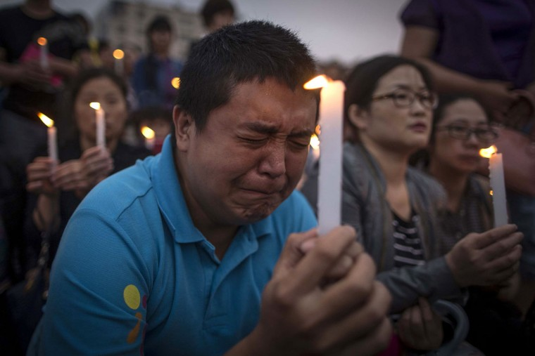 A man reacts during a candle light vigil by locals and family members of passengers onboard the capsized cruise ship in Jianli county in southern China's Hubei province Thursday June 4, 2015. Rescuers cut three holes into the overturned hull of a river cruise ship in unsuccessful attempts to find more survivors Thursday. (Chinatopix Via AP)