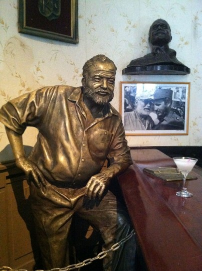"""This May 17, 2015 photo shows the El Floridita bar decorated with a statue of writer Ernest Hemingway, also pictured on the wall in a photo with Fidel Castro, in Old Havana, Cuba. For a drinking tour, consider Ernest Hemingwayís advice: """"My mojito in La Bodeguita, my daiquiri in El Floridita.î (AP Photo/Beth J. Harpaz)"""