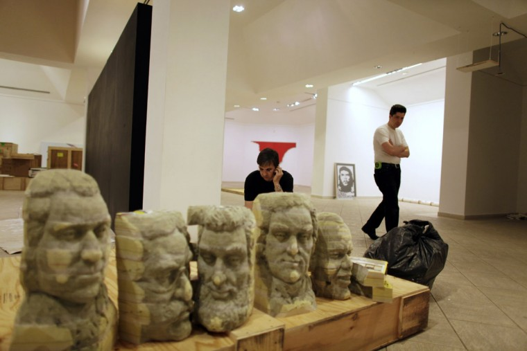 """FILE - In this March 20, 2009 file photo, US curator Alberto Magnan, center, speaks on his phone behind the """"New Mount Rushmore"""" sculpture at the National Museum of Fine Arts in Havana, CUBA. The piece is part of the """"Chelsea Visits Havana"""" exhibit, the largest collective display of contemporary American art in Cuba in nearly a quarter-century. (AP Photo/Javier Galeano, File)"""