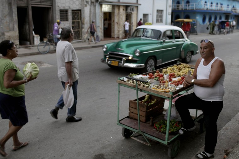 FILE - In this Dec. 3, 2013 photo, a self-employed fruit and vegetable vendor waits for customers in the street in Havana, Cuba. When traveling to Cuba bring cash to change into convertible pesos, also known as CUCs (not CUPs, the currency used by locals), and budget carefully. There are only a handful of ATMs in Havana and U.S. bank cards arenít currently accepted. (AP Photo/Franklin Reyes, File)