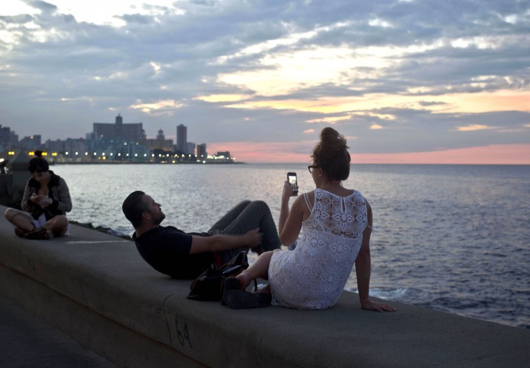 FILE - This Dec. 19, 2014 file photo shows tourists taking photos along the waterfront promenade known as the Malecon in Havana, Cuba. If you are old enough to remember traveling without credit cards, ATMs and smartphones, then visiting Cuba will be a trip back in time. (AP Photo/Ramon Espinosa)