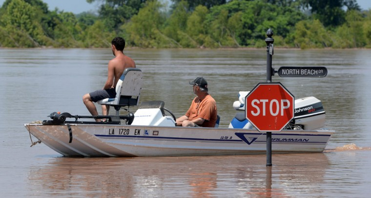 A boat makes it's way along North Beach Drive in the River Bluff subdivision of Bossier Parish, La., Saturday, June 6, 2015, after flooding from the Red River made the roads impassable. (Douglas Collier/The Shreveport Times via AP)