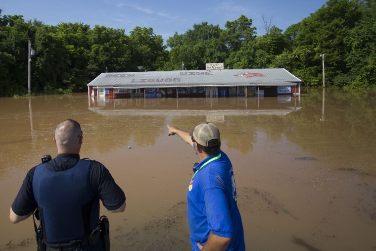 First responder monitor water levels at K&A Liquor store store near Garland City, Ark., Friday, June 5, 2015. Miller County Emergency Management evacuated Garland early Friday morning. Residents have been allowed back to their homes after pumps were uses to fill a relief pond stabilizing the levee. (Evan Lewis/The Texarkana Gazette via AP)