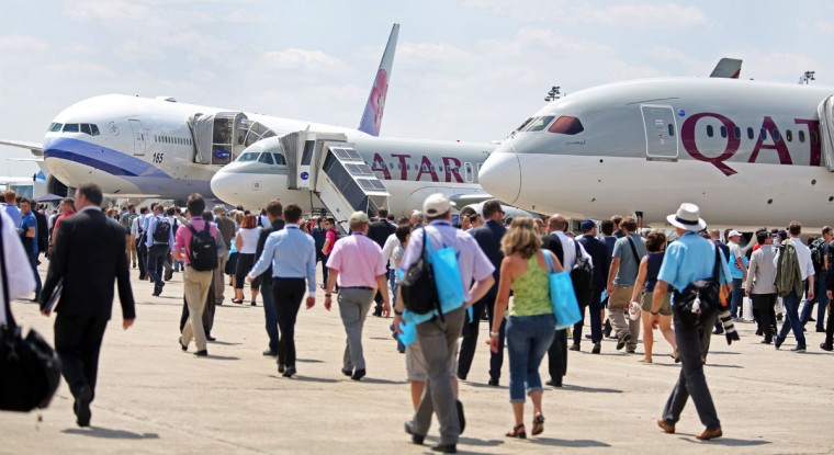 Visitors walk past planes at the Paris Air Show in Le Bourget, north of Paris, Wednesday June 17, 2015. Some 300,000 aviation professionals and spectators are expected at this weekís Paris Air Show, coming from around the world to make business deals and see dramatic displays of aeronautic prowess and the latest air and space technology. (AP Photo/Remy de la Mauviniere)