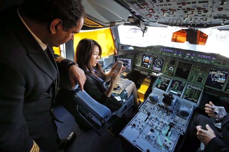 Visitors take photos during a press visit in the cockpit of the Airbus A380 of Qatar Airways presented at the Paris Air Show, in Le Bourget airport, north of Paris, Wednesday, June 17, 2015. Qatar Airways has brought 4 Airbus A380's in service since last year. (AP Photo/Francois Mori)
