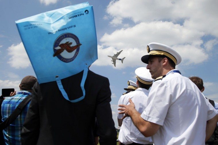 The Airbus A380 performs a demonstration flight as onlookers , one of them wearing a bag as a sun hat, at the Paris Air Show, in Le Bourget airport, north of Paris, Tuesday, June 16, 2015. Some 300,000 aviation professionals and spectators are expected at this weekís Paris Air Show, coming from around the world to make business deals and see dramatic displays of aeronautic prowess and the latest air and space technology. (AP Photo/Francois Mori)